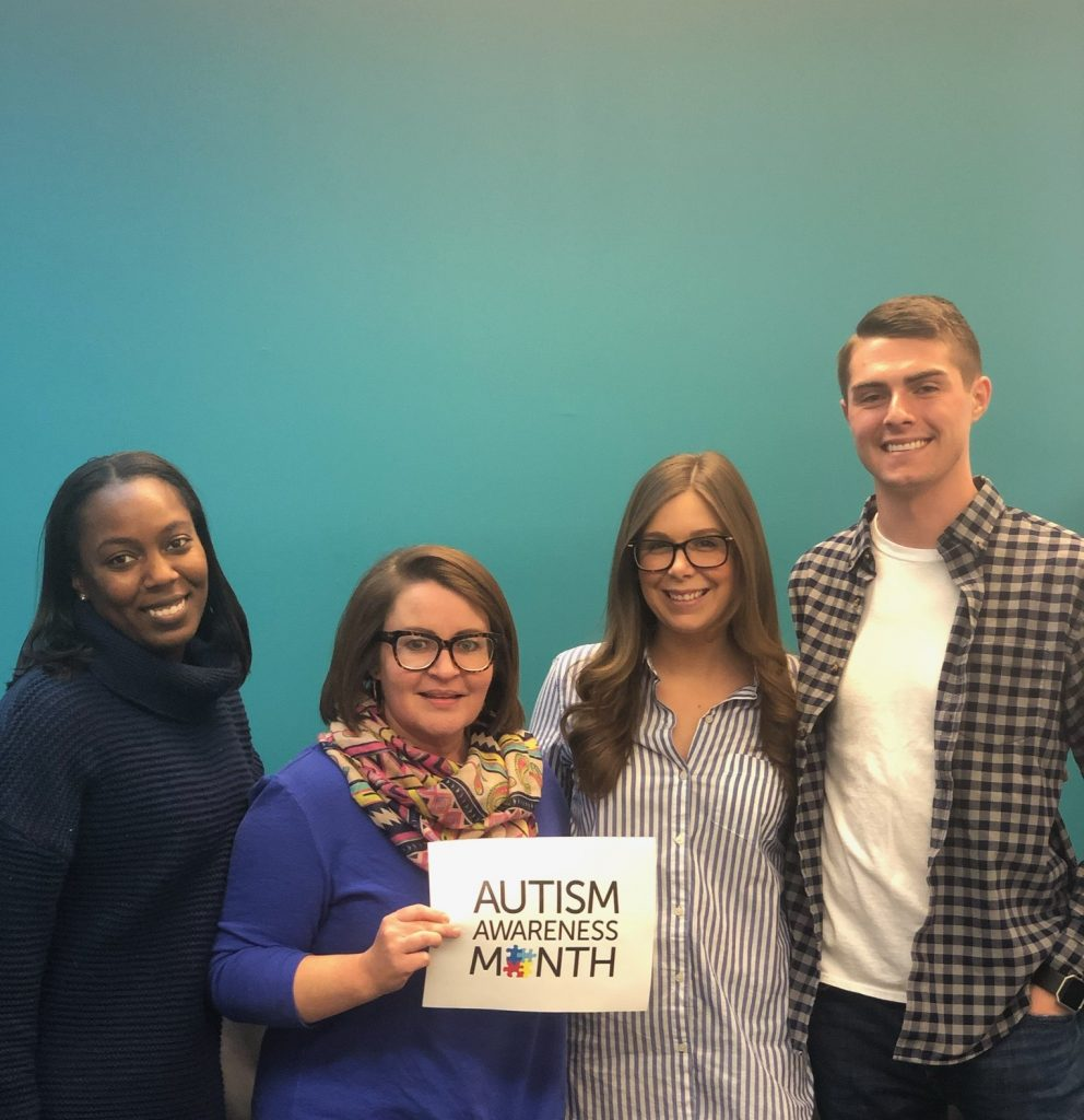 Chimes Holcomb staff hold Autism Awareness Month sign